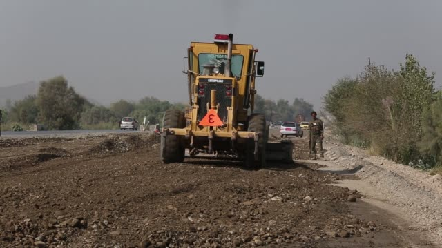 vídeos de stock e filmes b-roll de worker operates a caterpillar inc. motor grader at a road-building site on the torkham-jalalabad highway expansion project in nangarhar province,... - caterpillar inc