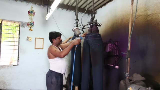 vídeos de stock, filmes e b-roll de a worker operates a fabric dyeing machines operate in a jeans factory at an apparel park in the mundargi industrial area of ballari karnataka india... - tintura
