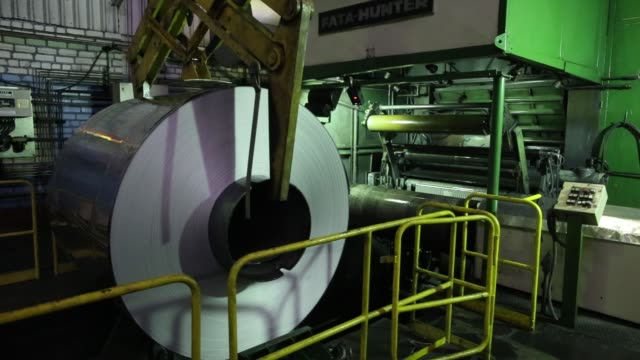 A worker operates machinery on the production line for aluminium foil at the Sayanal foil manufacturing plant operated by United Co Rusal in...