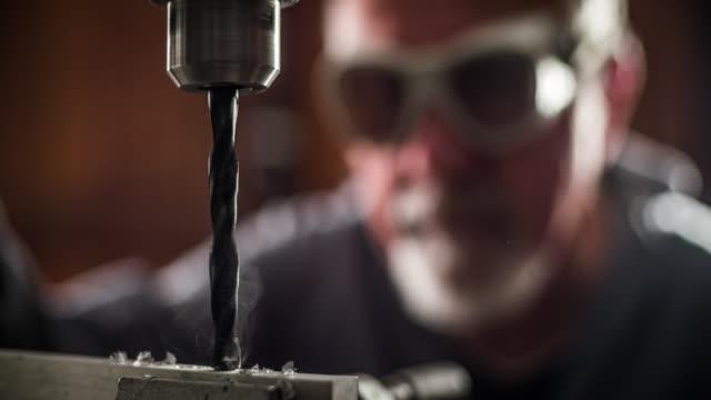 vidéos et rushes de travailleur d'un banc de machine de forage - atelier d'artisan