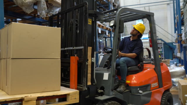 operaio che gestisce carrelli elevatori in magazzino distribuzione - azionare video stock e b–roll