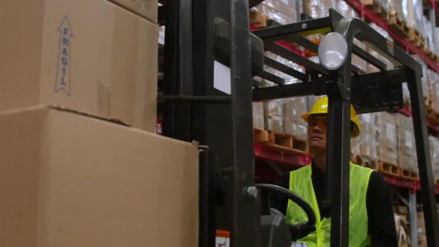vídeos de stock, filmes e b-roll de trabalhador operação de empilhadeira no armazém - caixa de papelão