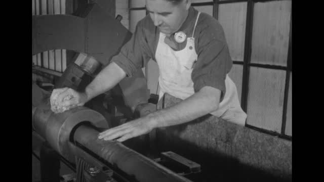 worker operating machine with gun barrel running through it / worker at machine holding rag, liquid covering barrel / note: exact day not known - gun barrel stock videos & royalty-free footage