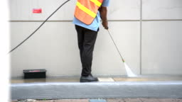 worker or cleaning staff is using a high-pressure water spray