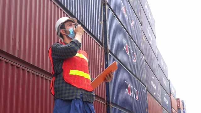worker or engineer wear protective mask prevent from covid-19 pandemic virus working at industrial factory with container for logistic import and export business - hard hat stock videos & royalty-free footage