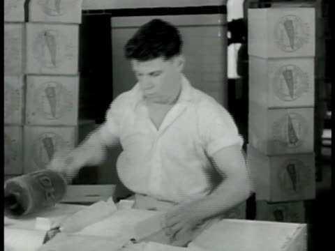 Worker packing butter into boxes labeling butter w/ roller stacks of boxes BG MS Worker sliding large mound of butter out of churning machine MS...