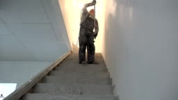 Worker Painting Ceiling With Roller in staircase