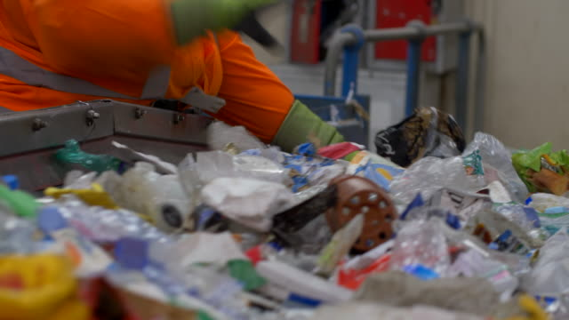 worker picks paper, plastics refuse and garbage on conveyor belts being sorted bags and other recycling waste sorted - manufacturing machinery stock videos & royalty-free footage
