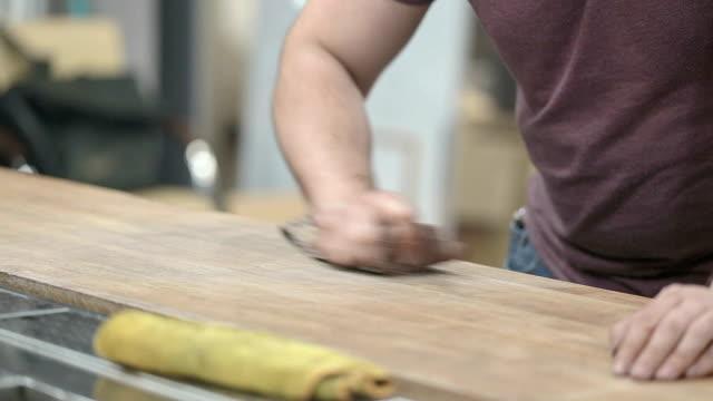 作業者はバーカウンターの木製の表面を磨きます。 - 挽く点の映像素材/bロール