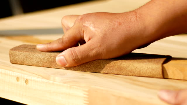 worker polishing wood table with sand paper with nature sunlight - carving craft activity stock videos and b-roll footage