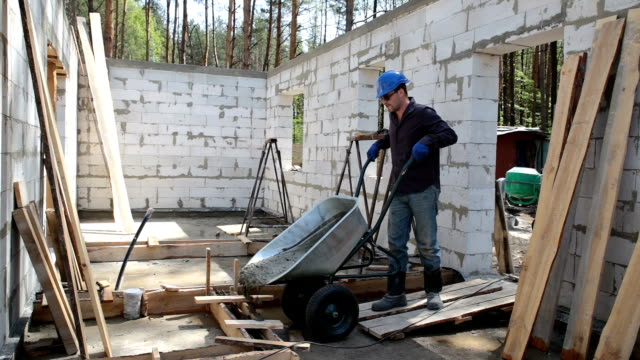 worker pouring concrete into a wooden formwork. - wheelbarrow stock videos and b-roll footage