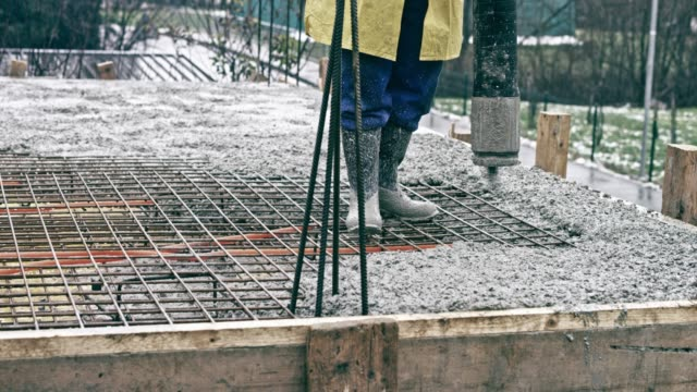 worker pouring concrete onto a rebar mesh on the first floor of the building - rod stock videos and b-roll footage
