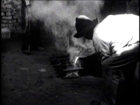 1930 ws worker pouring liquid silver into pan and steam rising / mexico city, mexico - lingotto video stock e b–roll