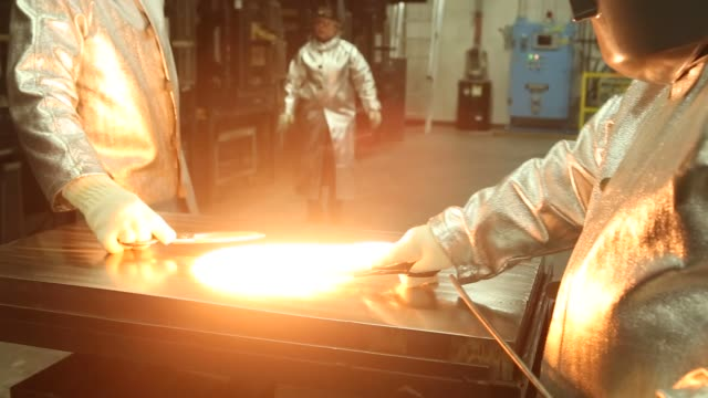 A worker pours a crucible of molten glass from a furnace at Corning Inc's Sullivan Park Science Technology Center in Corning New York Tuesday March...