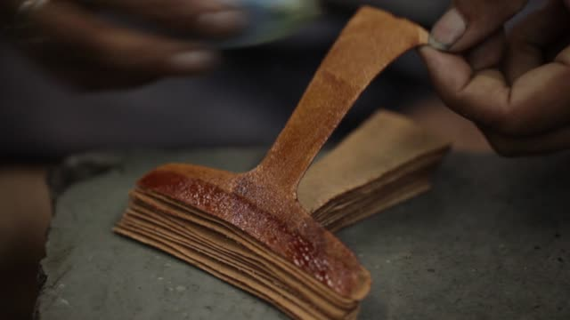 A worker prepares leather uppers for shoes at a workshop in Agra Uttar Pradesh India on Wednesday June 21 Workers prepare leather uppersfor shoes at...