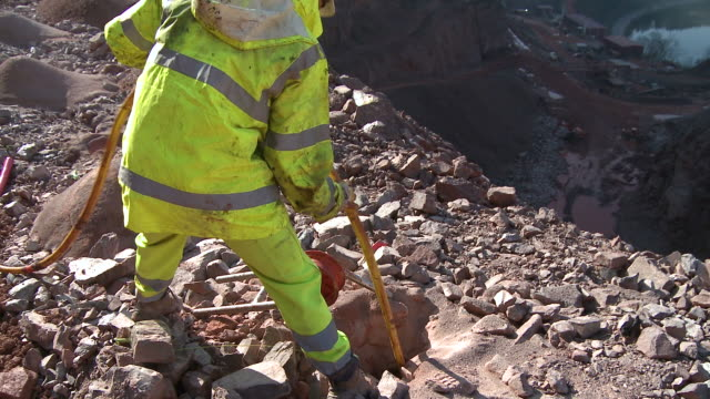 ms worker preparing blasting operation at quarry / taben-rodt, rhineland-palatinate, germany - 石切場点の映像素材/bロール