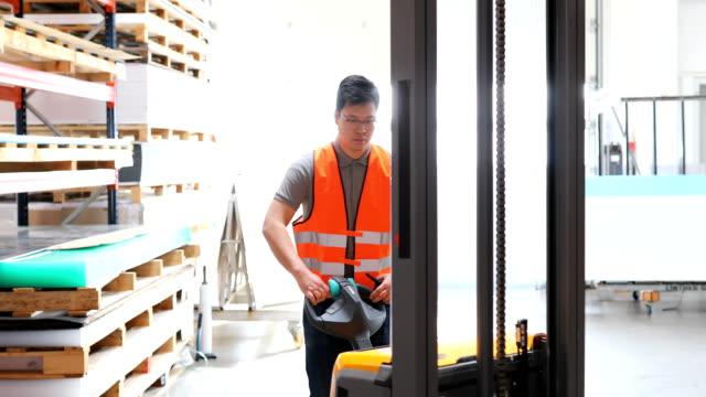 arbeiter ziehen maschinen im verteilerlager - hubwagen stock-videos und b-roll-filmmaterial