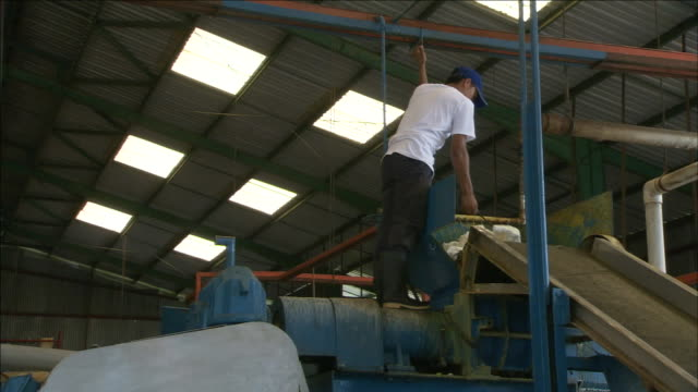 a worker pulls a sheet of rubber onto a conveyor. - sheet stock videos & royalty-free footage