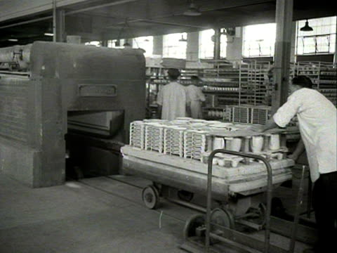 a worker pushes a trolley of vases into a kiln at a pottery - kiln stock videos and b-roll footage