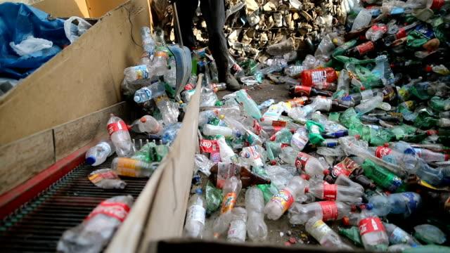 vídeos de stock, filmes e b-roll de o trabalhador empurra frascos plásticos com uma pá para recicl. trabalhando em uma fábrica de reciclagem - reciclagem