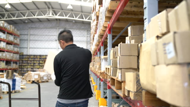 worker pushing boxes on hand truck in warehouse - removing stock videos & royalty-free footage
