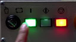 Worker pushing button to start automatic machine.