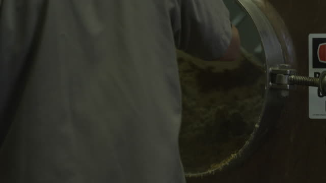 Worker pushing grain out of vat with shovel