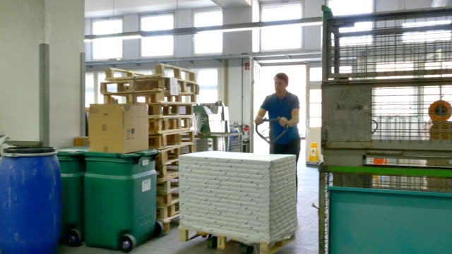 Worker pushing packages on hand truck at factory