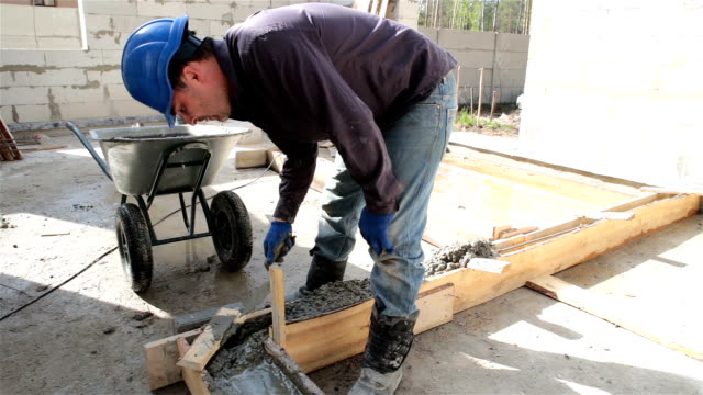worker puts concrete in the formwork with the help of a masonry trowel. - wheelbarrow stock videos and b-roll footage