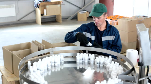 worker puts finished products in a box from a production line. - bottling plant stock videos & royalty-free footage