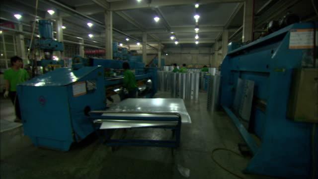 WS Worker putting metal sheets into machine to make solar hot water heaters, Dezhou, Shandong, China