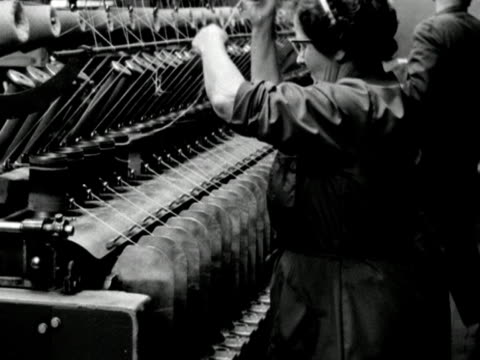 a worker removes full bobbins of wool from a machine in a wool mill - 織物工場点の映像素材/bロール