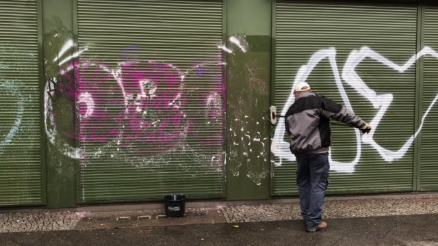 A worker removes graffiti by scrubbing it with a chemical and later blasting it with highpressure hot water in the city center on November 14 2017 in...