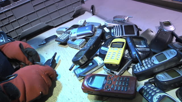 cu worker removing batteries from used cell phones that come to facility for refurbishing or recycling / dexter, michigan, usa - dismantling stock videos & royalty-free footage