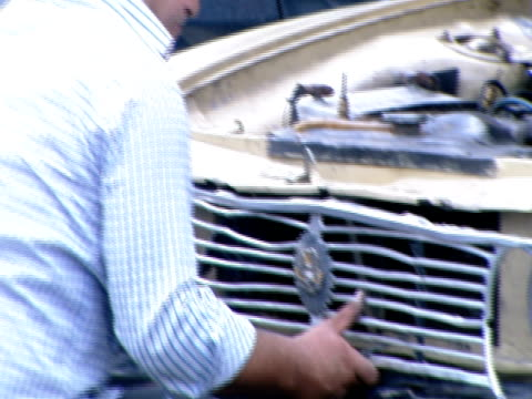 zi worker repairing the grill of a pickup truck in a storefront parking lot while others are watching / tehran, tehran, irn - centro commerciale suburbano video stock e b–roll