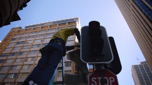 Worker repairs traffic light