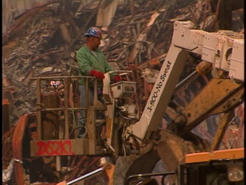 vidéos et rushes de worker rides in the bucket of construction equipment, suspended over a mountain of rubble at ground zero of the world trade center. - style des années 2000