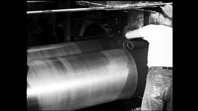worker rolling rubber at machine inside factory - 1940 1949 bildbanksvideor och videomaterial från bakom kulisserna