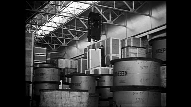 stockvideo's en b-roll-footage met worker rolling spool of cable into storage yard full of spools; animation of supply lines coming out of a factory spread across the map; workers with... - 1940 1949