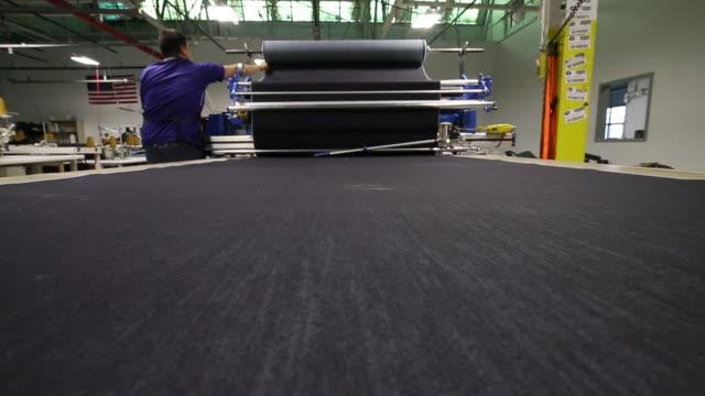 worker rolls denim onto long table during jeans manufacturing at dearborn denim in chicago, illinois, november 8, 2017. photographer: jim young - trousers stock videos & royalty-free footage