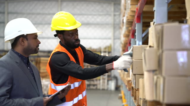 Worker scanning boxes by manager in warehouse
