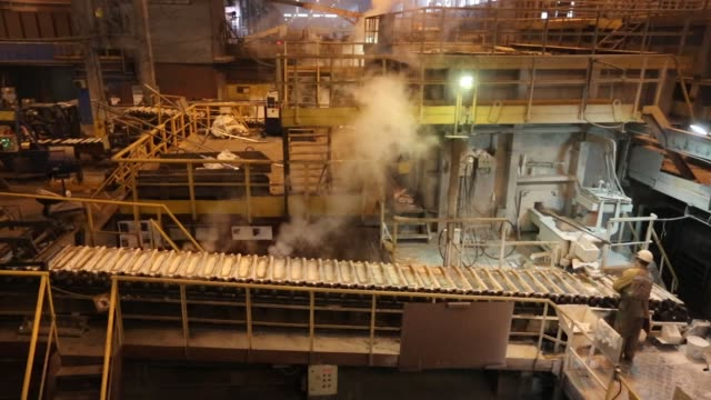 a worker scrapes off the top layer as molten aluminum cools in ingot moulds in the foundry at the krasnoyarsk aluminum smelter operated by united co... - foundry worker stock videos and b-roll footage