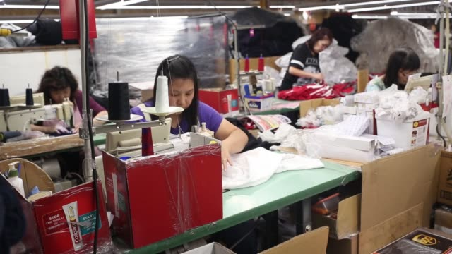A worker sews a Canadian maple leaf to a shirt at the WS Co factory in Toronto Ontario Canada on Friday June 9 2017 Shots view of many people using...