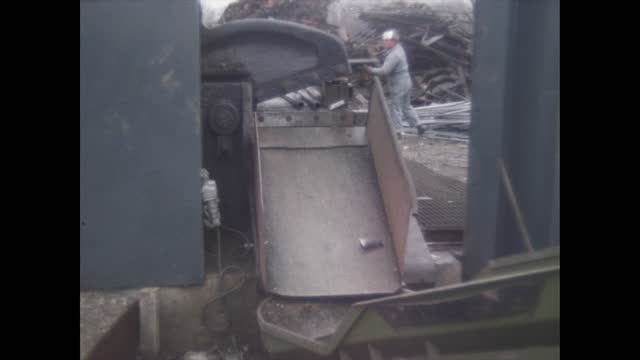 worker shifts scrap pipe to guillotine for processing in junk yard - execution stock videos & royalty-free footage