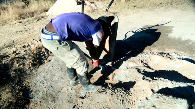 cu worker shovelling sand into water to mix concrete at a rural building site cape town is located on the western coast and isthe second largest city... - 迫撃砲点の映像素材/bロール