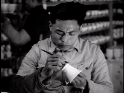 1944 ms worker sitting at factory bench making porcelain cup with other workers in the background / china - porcelain stock videos & royalty-free footage