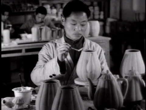 1944 ms worker sitting at factory bench making porcelain decanters with other workers in the background / china - porcelain stock videos & royalty-free footage