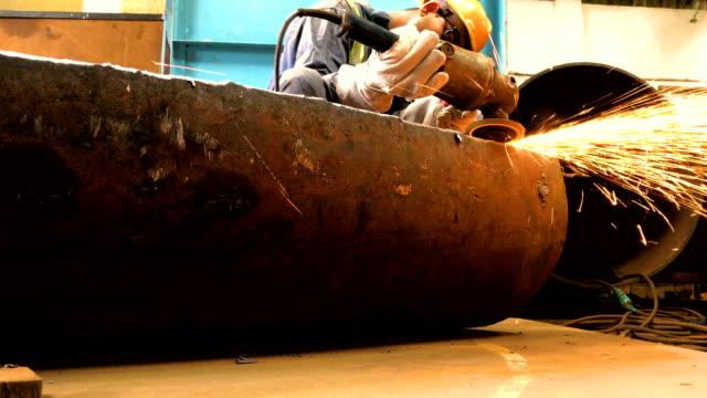 Arbeiter, die Glättung der Metalloberfläche mit einer Schleifmaschine