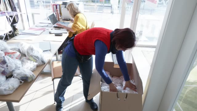 stockvideo's en b-roll-footage met worker sorts out made protective masks for later be distributed to homeless and those in need at the berliner stadtmission charitable organization on... - number 9
