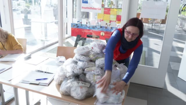 worker sorts out made protective masks for later be distributed to homeless and those in need at the berliner stadtmission charitable organization on... - number 9 video stock e b–roll